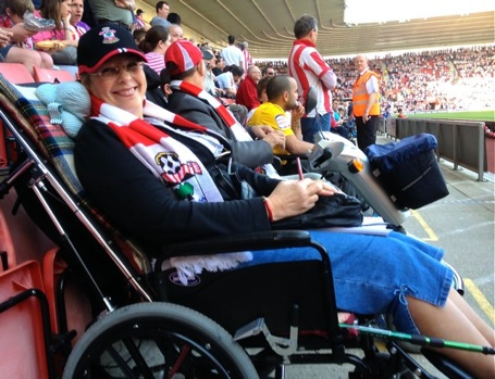 Image of Elizabeth in a football crowd, pitch-side; at a Southampton Saints game taking a break from writing