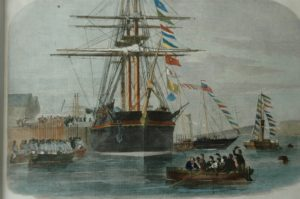 After USS (formerly HMS) Resolute sailed across the Atlantic by Captain Henry Julius Hartstene, Queen Victoria asked to have Resolute towed to Cowes so she could visit the ship and receive her from Captain Hartstene. Queen Victoria and her family are walking across to the ship, while lighters in the foreground are filling with cheering people