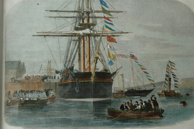 The tall ship Resolute at the pier, and Queen Victoria, Prince Albert, and many other people are crossing the gangplank to enter the ship. Resolute is in full dress with her signal flags flying up through her rigging, and is surrounded by small boats so of which are also have their signal flags strung up to the top of their masts, and which are full of people, waving and raising their hats to the Queen